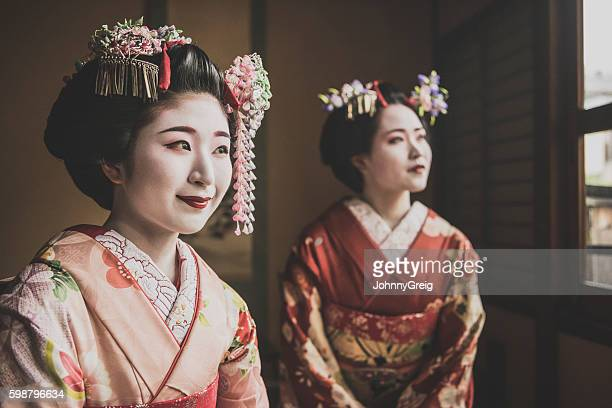 Two young maiko in traditional make up and kimonos, smiling