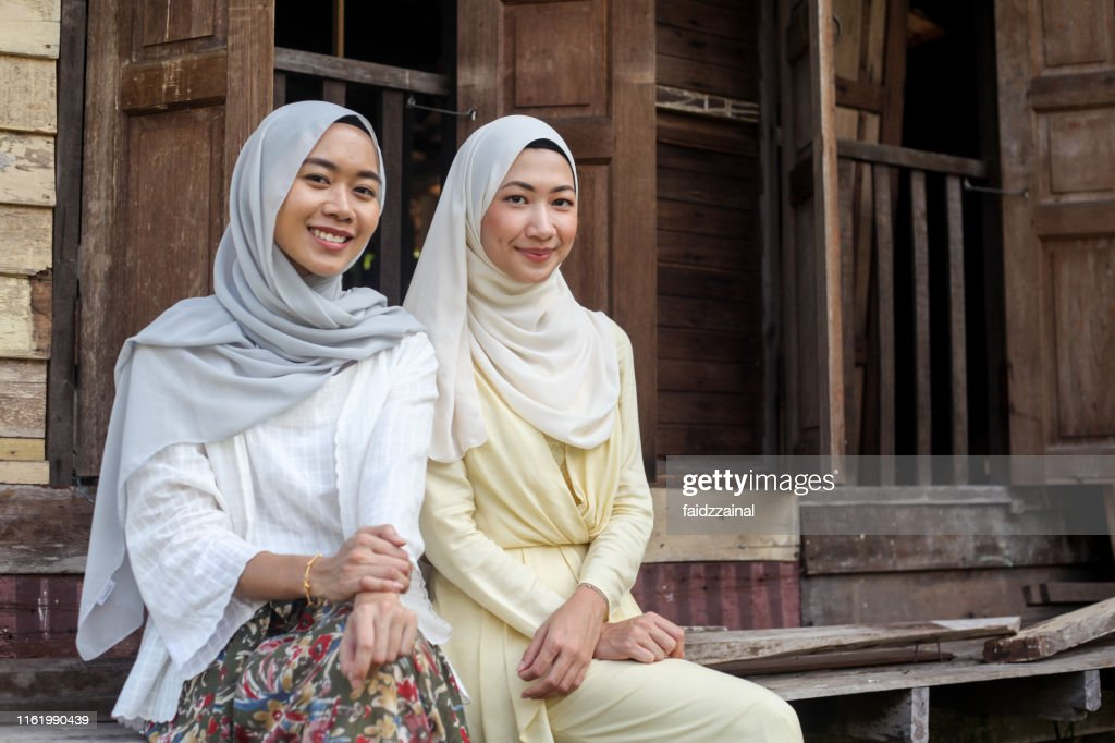 Two Young Malay Muslim Women Sitting Together : Stock Photo