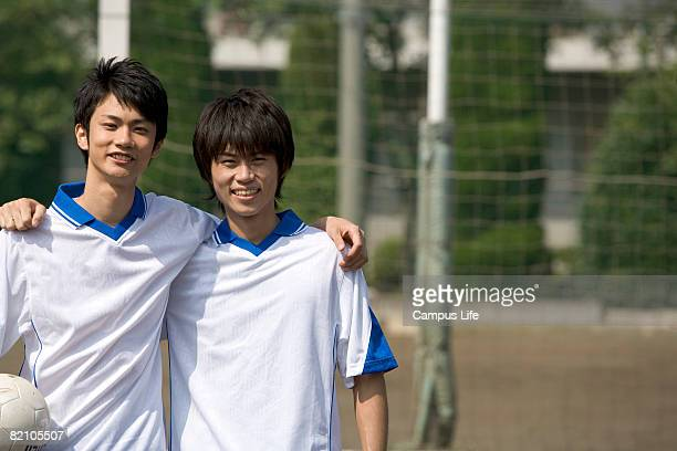 Two young male adults standing in front of goal post