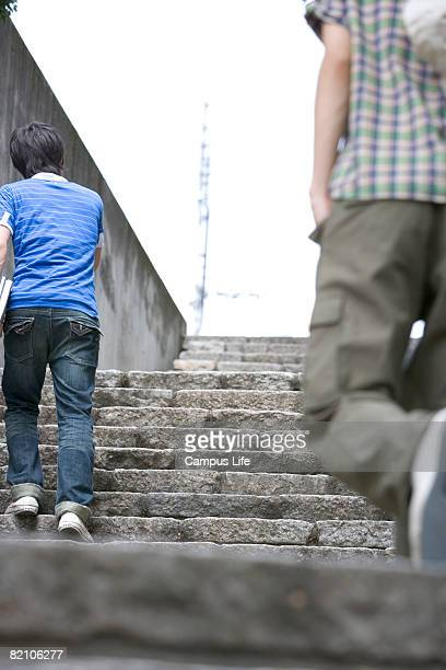 two young male adults walking up the stairs, rear view - só homens jovens imagens e fotografias de stock