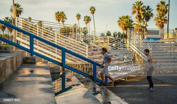 two young male athletes doing steps running on the outdoor public stadium - alex potemkin or krakozawr latino fitness stock photos and pictures