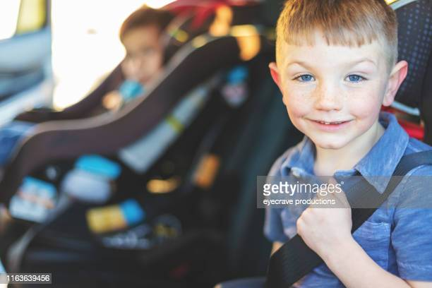 Two Young Male Children strapped in safety carseats and strapped in seat belts in automobile looking at camera