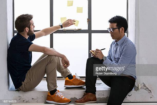 two young male designers sharing ideas on post it notes - robin skjoldborg stock pictures, royalty-free photos & images