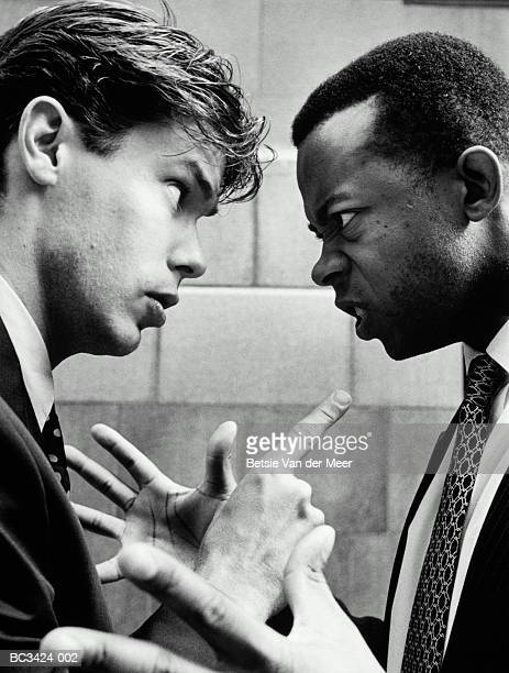 Two young male executives arguing, close-up (B&W)