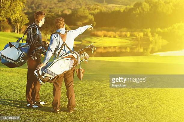Two young male golfers pause on idyllic golf course