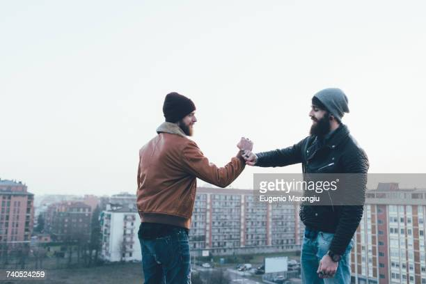 two young male hipsters fist bumping above cityscape - fist bump stock pictures, royalty-free photos & images