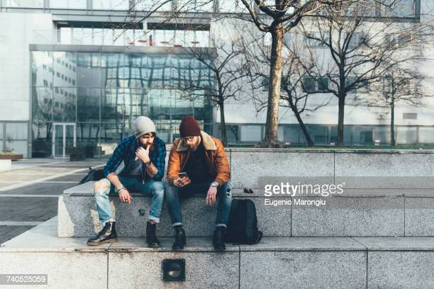 Two young male hipsters sitting on wall looking at smartphone