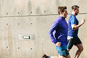 Two young male runners running along city sidewalk