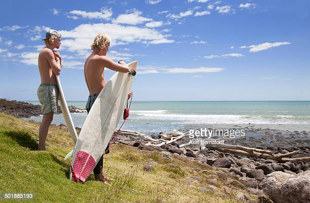 Two young male surfer friends watching sea