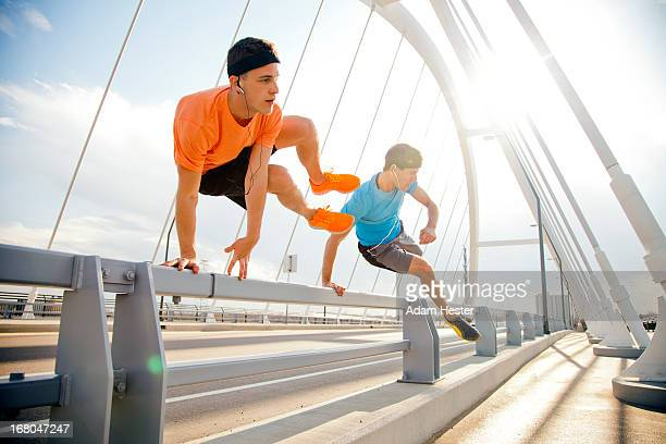 Two young males jogging in a urban area together.