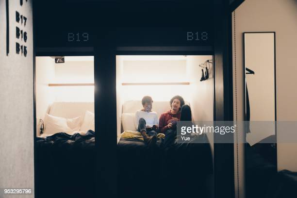 Two young man and woman talking on bed of capsule hotel