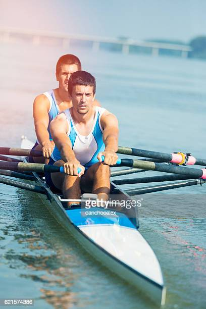 Two young man rowing on the river