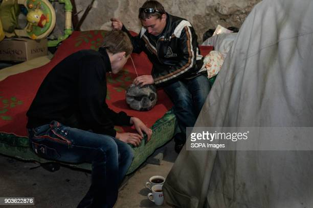 Two young man trying to repair their soccer ball with basic sewing kit The conflict between the Russian backed rebels and the Ukrainian arm forces in...