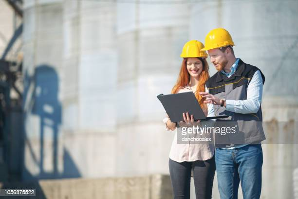 Two young managers talking in front of silo