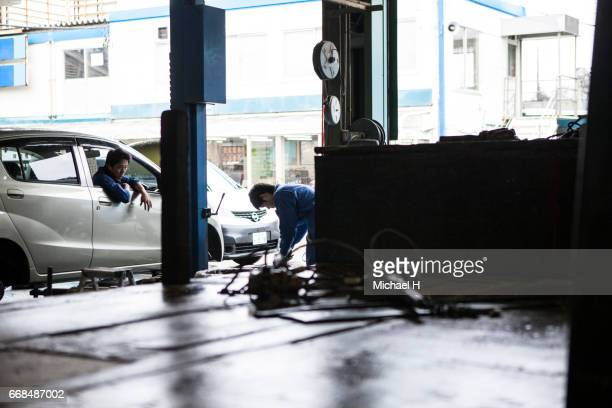 two young mea working in the automobile restoration workshop - auto repair shop exterior stock pictures, royalty-free photos & images