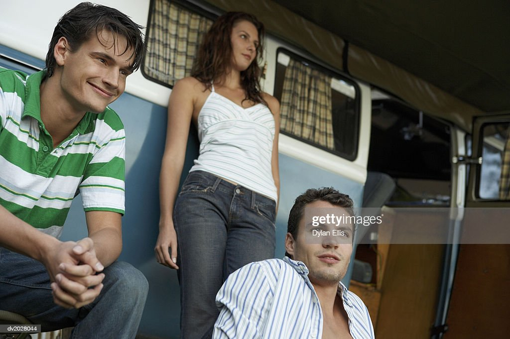 Two Young Men and a Woman by a Motor Home : Stock Photo