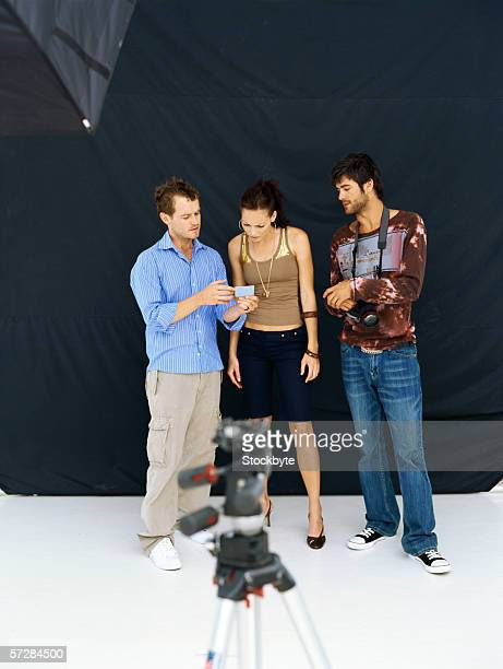 Two young men and a young woman looking at a photograph