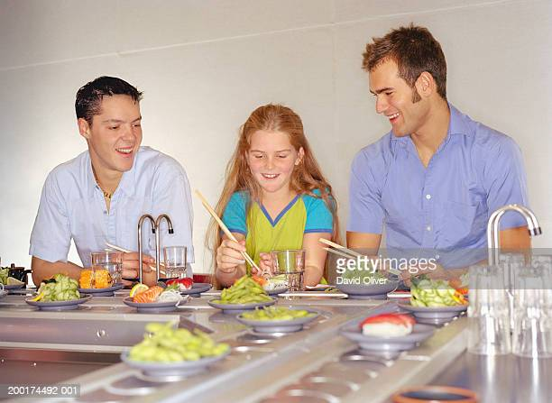 Two young men and girl (10-12) eating at sushi bar