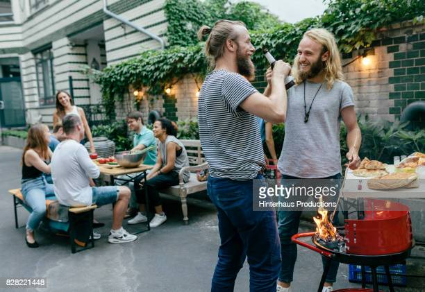 two young men and their friends catching up over a barbecue - men friends beer outside stock pictures, royalty-free photos & images