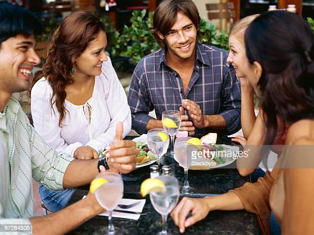 two young men and three young women sitting at a restaurant table - petit ami photos et images de collection