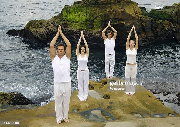 Two young men and two young women practicing yoga in the tree pose