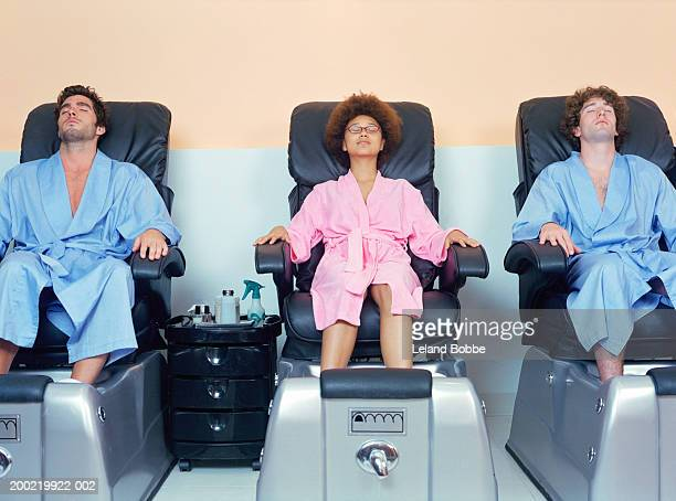 Two young men and woman at spa soaking feet before pedicure