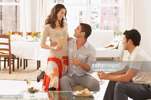 Two young men and woman by coffee table, woman leaning on one man, laughing