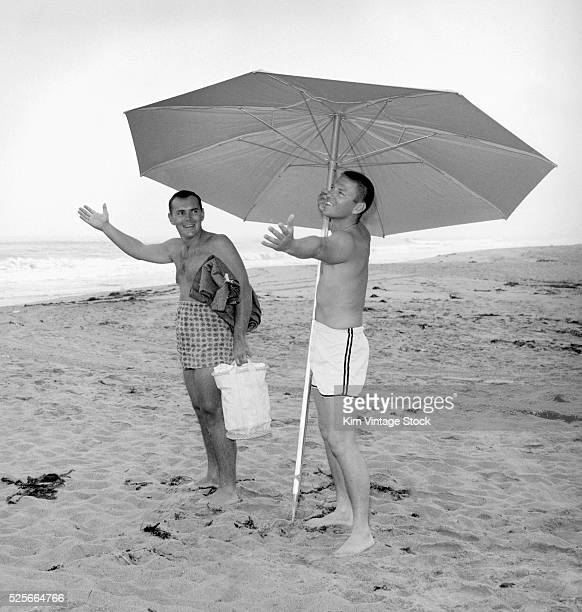 Two young men appear to check for rain or sunshine from underneath their beach umbrella in Southern California