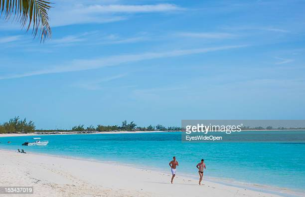 Two young men are running at the beach of luxury Resort and Hotel Cape Santa Maria which is having one of the Bahamas´ best beaches with white sand...