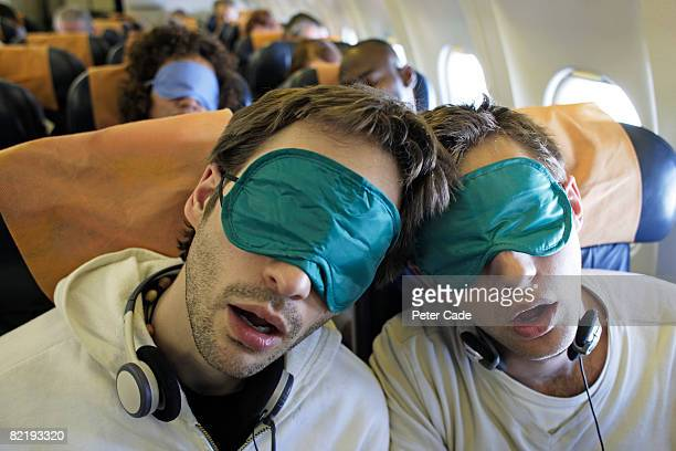 Two young men asleep on plane