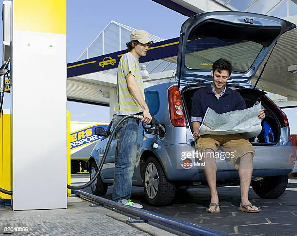 two young men at petrol station, reading map and filing car
