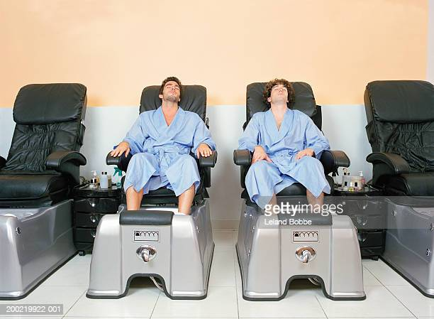 two young men at spa soaking feet before pedicure - pedicure stock pictures, royalty-free photos & images