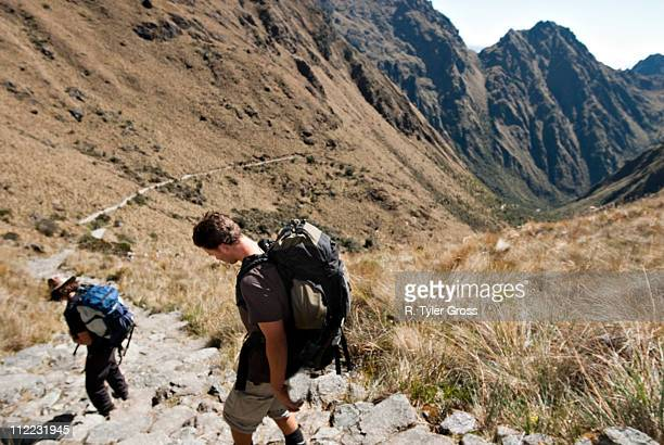 two young men begin the decent from dead woman's pass to camp three on the inca trail. - bezirk cuzco stock-fotos und bilder