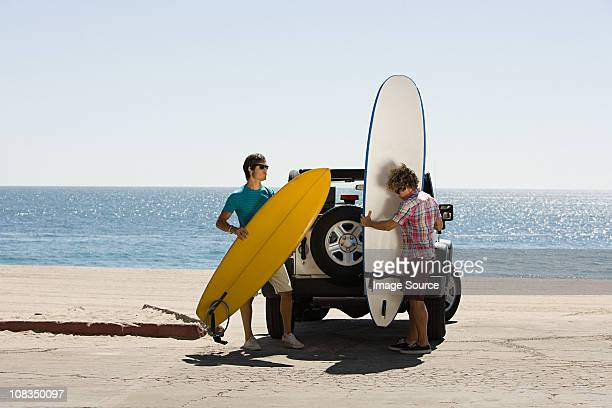 Two young men by SUV with surfboards