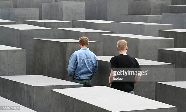 zwei junge männer mit dem holocaust memorial in berlin, deutschland - denkmal stock-fotos und bilder
