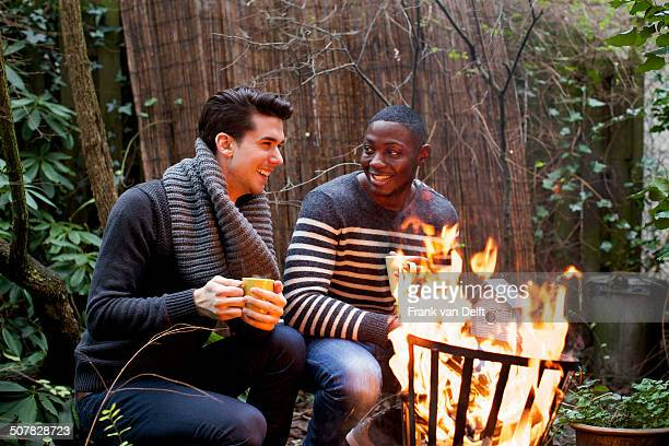 Two young men crouching in front of garden fire with coffee