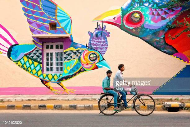 Two young men cycling by a colorful mural street art in New Delhi India