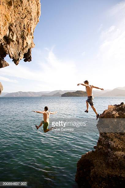 Two young men diving off rock into sea, mid-air, rear view