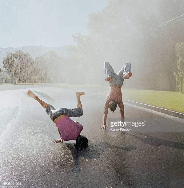 Two young men doing handstands in rain