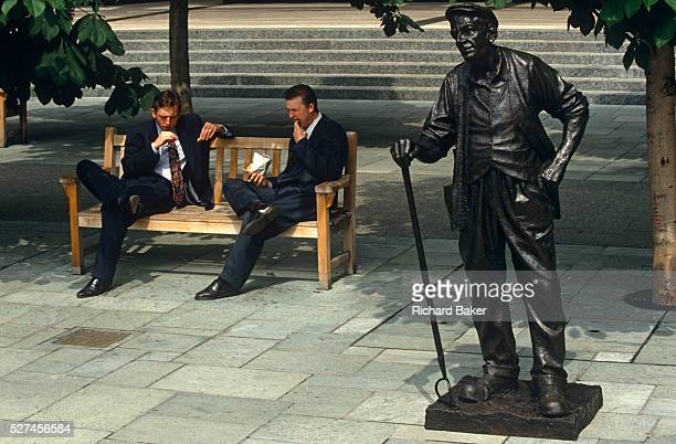 Two young men dressed in office suits casually stuff their lunches during a hot lunchtime break in the Broadgate Estate in the City of London Both...