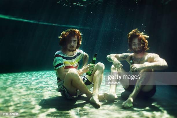 Dos hombres jóvenes bebiendo cerveza en la piscina