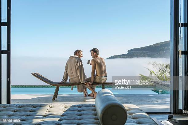 Two young men drinking coffee at the poolside