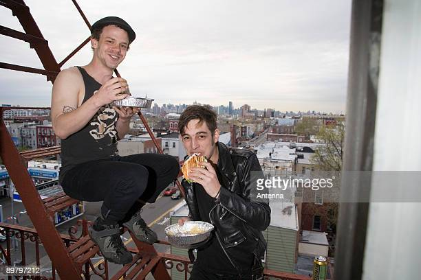Two young men eating take out food on a fire escape