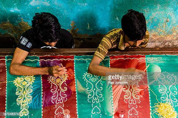 Two young men embroider a piece of cloth at a Bihari community.Bihari's are the Urdu speaking Muslim community in Bangladesh. At the time of The...