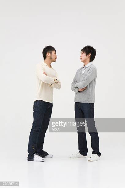Two young men glaring at each other