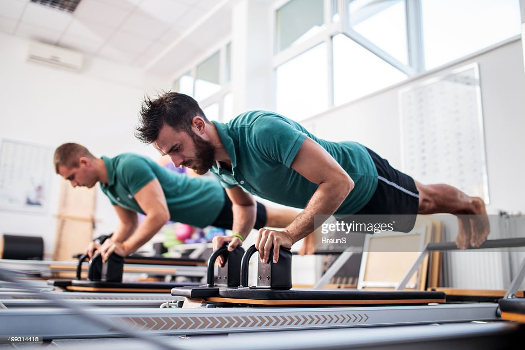Two young men having a Pilates class at health club. : Stock Photo