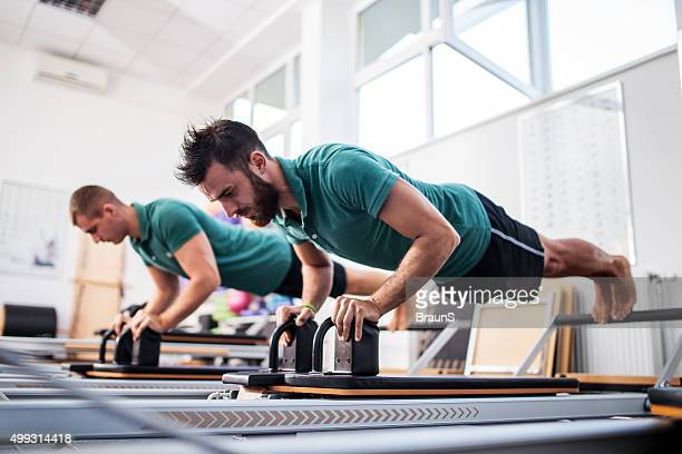 Two young men having a Pilates class at health club.