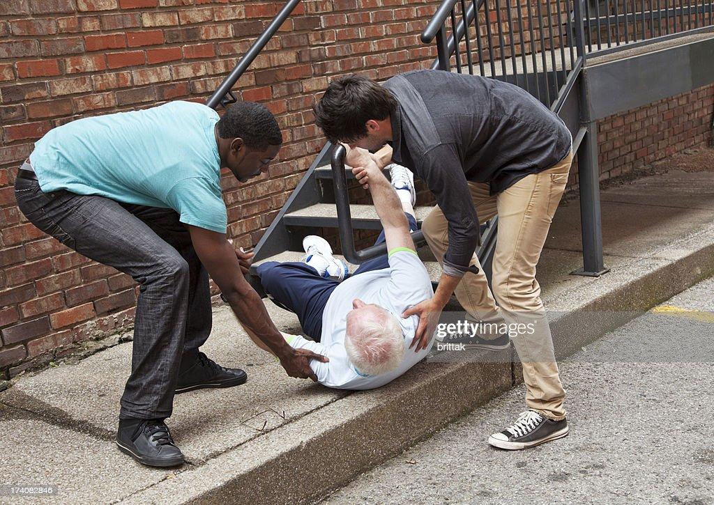 Two young men helping fallen down senior. Multi ethnic : Stock Photo