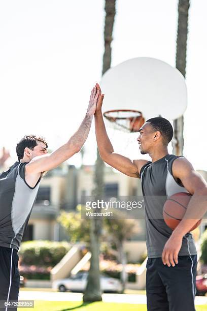 Two young men high-fiving on outdoor basketball court