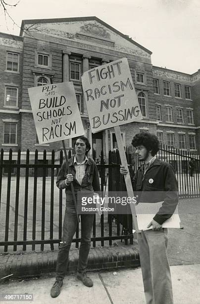 Two young men hold protest signs outside South Boston High School in Boston Mass on Sept 12 the first day of school under the new busing system put...